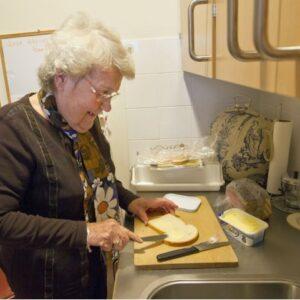 mevrouw in de keuken een boterham smeert