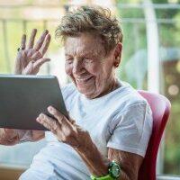 Mevrouw zwaait vrolijk naar iemand op haar tablet