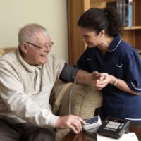 Wijkverpleging meet bloeddruk bij meneer