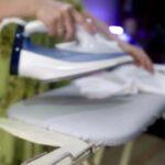 Vrouw die kleren aan het strijken is