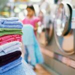 Stapel schone handdoeken op de voorgrond en een wasserette op de achtergrond.